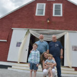 Paul and Meredith Blakesley, their sons, William and Oliver, and Meredith's father, Jim Grimes, stand in front of The Lakeside Barn, a new event venue at Duck Puddle Campground in Nobleboro. The Blakesleys and Jim and Mary Grimes own the campground.