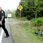 Officer Larry Hesseltine of the Waldoboro Police Department investigates the scene of a truck and bicycle collision on Route 1 in Waldoboro on Wednesday.