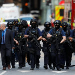 Armed police officers walk outside Borough Market after an attack left 6 people dead and dozens injured in London on June 4, 2017.