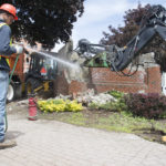 A Bangor Department of Public Works crew demolished the water fountain in Pickering Square on Tuesday. Crew member Jeremy Lampher sprays water to keep dust down.