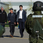 Canadian Prime Minister Justin Trudeau and Quebec Premier Philippe Couillard (L) walk with Gatineau resident Michel Papineau (2nd L) as they make their way to a military helicopter in Ottawa, Canada, May 11, 2017.