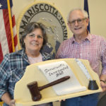 "Damariscotta Board of Selectmen Chair Robin Mayer and Vice Chair Ronn Orenstein hold a 1959 wood carving by the late Damariscotta artist Maurice ""Jake"" Day. The carving, along with the town seal behind Mayer and Orenstein, were both carved by Jake Day in 1959 and recently restored by his grandson Dan Day."