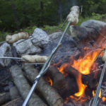 """If you have skewers or """"marshmallow sticks,"""" wrap some pretzel dough around them and slowly roast the pretzel over the coals until it's golden brown."""