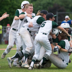 The Old Town Coyotes celebrate after their 6-5 victory over Erskine Academy to win the Class B North title at Mansfield Stadium in Bangor on Tuesday afternoon.