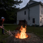 Josh Parda, a volunteer with Comins Hall, feeds the fire as he prepares to make bean-hole beans early Friday morning in Eddington. Parda is one of a group of volunteers who organize suppers, pie and bean sales and other events to generate income for the upkeep of the building that was built in 1878.