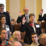 Maine senators raise their right hands as they are sworn in during the first session of the 128th Legislature.