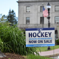 A sign encouraging University of Maine fans to purchase season memberships for the Black Bear men's hockey team is placed in a traffic island in downtown Bangor not far from City Hall.