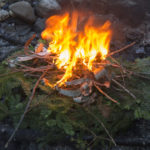 Creating a base with live evergreen boughs, then building up the campfire with dry wood of different types, including plenty of hardwood, helps create a good bed of coals for cooking. If you have trouble getting the fire to catch, try using dry birch bark gathered from fallen trees.