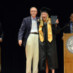 Lincoln Academy senior Esther Martin receives her diploma in a black graduation gown from adviser Robert Breckenridge on June 1, as Head of School David Sturdevant (left) and Associate Head of School Andy Mullin look on.