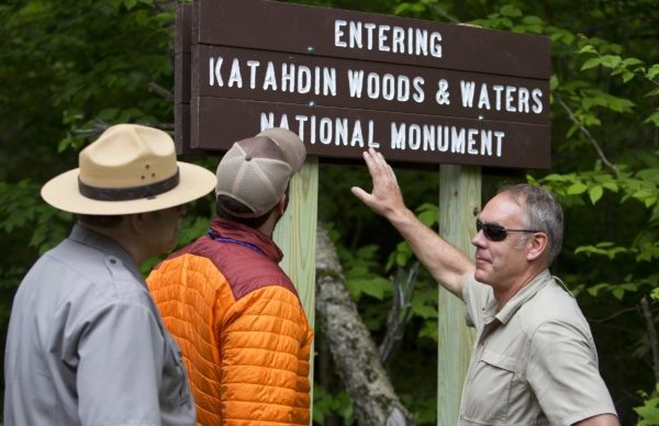 U.S. Secretary of the Interior Ryan Zinke (right) looks at the sign for the Katahdin Woods and Waters National Monument with Lucas St. Clair (center) and superintendent of Katahdin Woods Tim Hudson during a tour of the Katahdin Woods and Waters National Monument Wednesday.