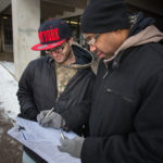 Ralph Tripp, 32, of Bangor and Maurice Gunn coordinate on a signature-gathering effort on a 2016 referendum for a York County casino outside the garage at Pickering Square in Bangor in January 2016.