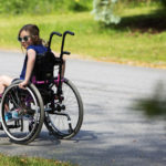 TOPSHAM, Maine -- 06/13/2017 - Wynter Przybylski, 9, looks over her shoulder to see where her nurse, Stephanie Shapiro, is while making their way home after school in Topsham Tuesday. Przybylski will spend the rest of her life in a wheelchair due to a misdiagnosis in February 2014. Przybylski was suffering from a common type of childhood leukemia in when she was misdiagnosed with severe constipation. Wynter has been treated successfully for the leukemia but because treatment was delayed, she developed a white blood cell clot on her spine that caused permanent paralysis. She has been awarded $1.9 million in a legal settlement. Ashley L. Conti | BDN