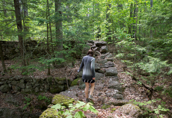 Rachel Borch, 21, walks over a stone bridge as she makes her way to the trail she was running on when she was recently attacked by a rabid raccoon near her home in Hope. The raccoon lunged at her and bit her on the thumb, not letting go. Borch drowned the animal in a puddle.