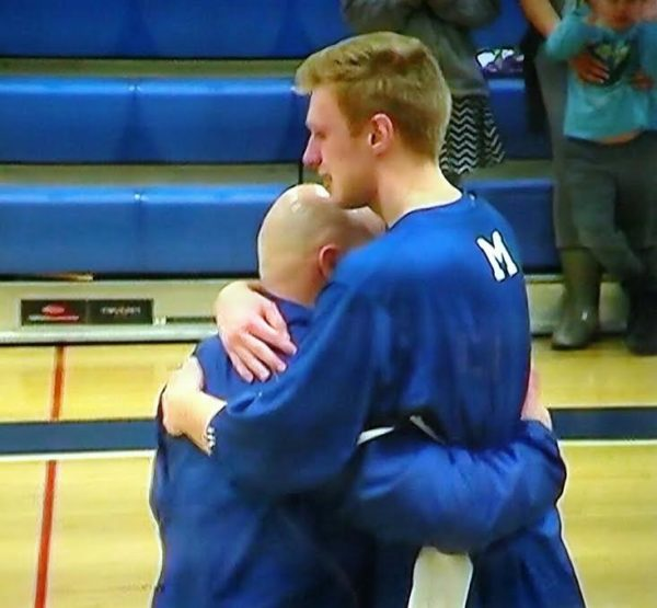 Morse High School varsity boys basketball coach Brian Bennett embraces senior Alex Fernald at the school's Senior Night this spring.