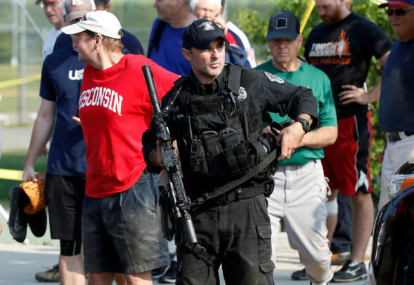 A U.S. Capitol police SWAT team officer escorts members of Congress and congressional staff from the scene after a gunman opened fire on Republican members of Congress during a baseball practice near Washington in Alexandria, Virginia, June 14, 2017.