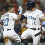 Houston's Jose Altuve (left) celebrates with teammate Carlos Correa after hitting a home run during the third inning Saturday against Boston at Minute Maid Park.