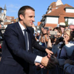 French President Emmanuel Macron (left) shakes hands with people outside the city hall where he votes  in the second round parliamentary elections in Le Touquet, France, June 18, 2017.