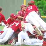 In the center Bangor High School Assistant baseball Coach, Tim Bush celebrates with the team after defeating Falmouth High School for the class A State Championship, Saturday at Fred Morton Field in Augusta.