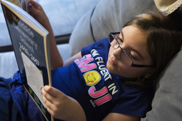 Wynter Przybylski, 9, looks over her elementary school yearbook at her home in Topsham. Przybylski will spend the rest of her life in a wheelchair due to a misdiagnosis in February 2014.