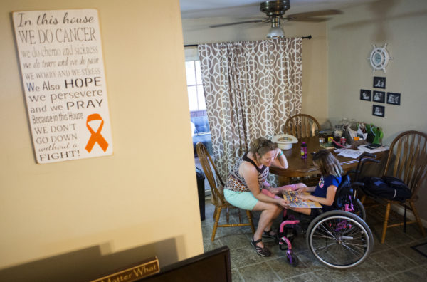 Wynter Przybylski (right), 9, shows Stephanie Shapiro her elementary yearbook at her home in Topsham. Przybylski will spend the rest of her life in a wheelchair due to a misdiagnosis in February 2014.