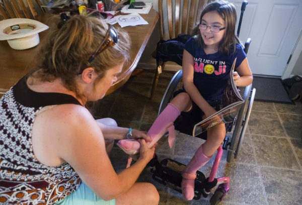 Stephanie Shapiro (left) massages the feet of Wynter Przybylski, 9, before putting her leg braces on at her home in Topsham. Przybylski will spend the rest of her life in a wheelchair due to a misdiagnosis in February 2014.