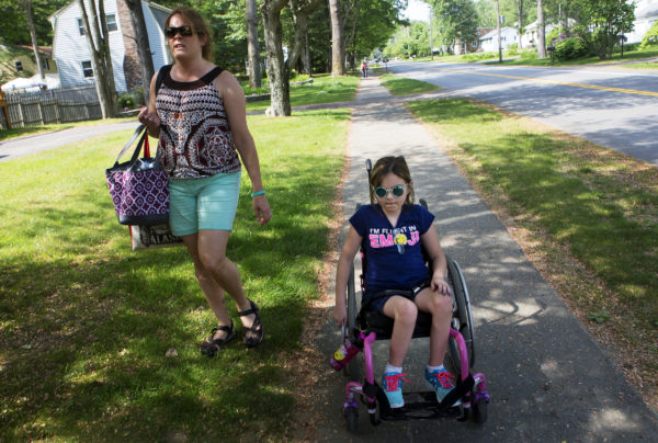 Wynter Przybylski (right), 9, makes her way home with her nurse, Stephanie Shapiro, at her home in Topsham Tuesday. Wynter has been treated successfully for the leukemia but because treatment was delayed, she developed a white blood cell clot on her spine that caused permanent paralysis. She has been awarded $1.9 million in a legal settlement.