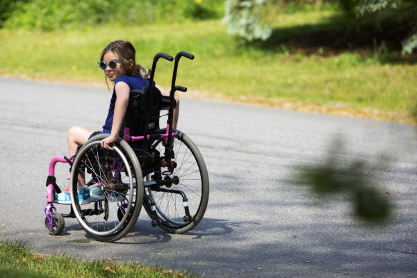 Wynter Przybylski, 9, looks over her shoulder to see where her nurse, Stephanie Shapiro, is while making their way home after school in Topsham Tuesday. Przybylski will spend the rest of her life in a wheelchair due to a misdiagnosis in February 2014.