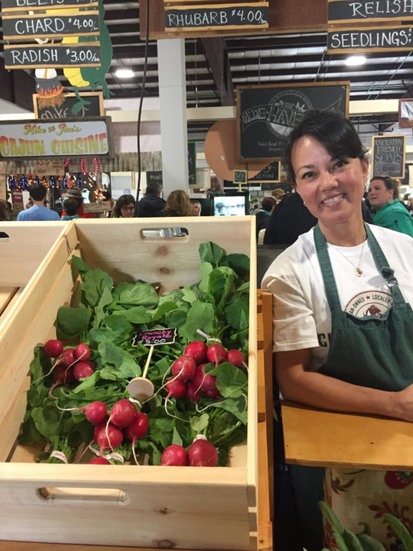 Anne Weinberg of Chase Stream Farm in Monroe smiles next to some of the produce she was selling recently at the new United Farmers Market of Maine in Belfast. Thanks to recently enacted food sovereignty legislation, small producers like Weinberg will have an easier time selling their products locally.