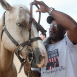 Willie gets his bridle put on by Cliff Burton, Navy Iraq veteran, as veterans gather to participate in the Horses and Heroes program, May 3, 2012, in Orlando, Florida.