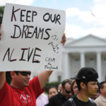 People hold signs outside the White House in Washington, D.C., during a rally to celebrate President Barack Obama's announcement that his administration will be granted deferred action and work permits to DREAMers end deportations and urge relief by governmental agencies for those in deportation proceedings, Friday, June 15, 2012.