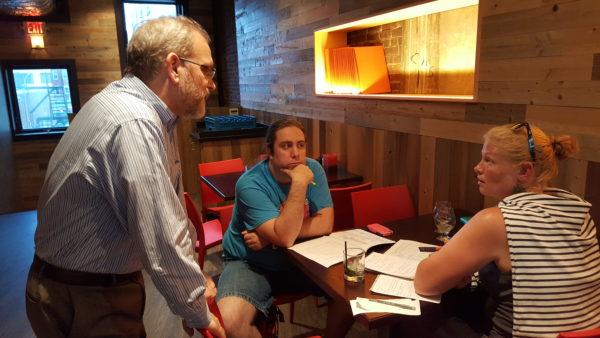 Bangor Savings Bank Senior Vice President Scott Blake gives project idea advice to Bangor residents Aubrae Ramiak and Jared Hunnefeld of the Innovative Communities competition's Abraham Lincoln School team on June 20 at the Blaze restaurant in Bangor.