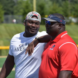 New England Patriots defensive lineman Woodrow Hamilton (left) shares a light moment with former Patriots running back Harold Shaw during Thursday's Football For You youth clinic held at the Winkin Complex at Husson University in Bangor.