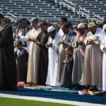 Men bow their heads facing east while Imam Younus Alfayyadh leads the prayers at Fitzpatrick Stadium in Portland on as local Muslims celebrated Eid al-Fitr, July 6, 2016.