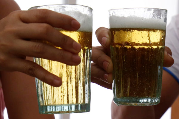 Customers hold glasses of beer at a restaurant