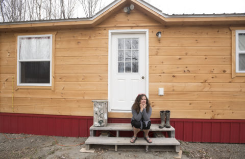 Mary Leaming sits in front of her tiny home that is nearly complete.
