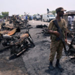 A soldier stands guard amid burnt out cars and motorcycles at the scene of an oil tanker explosion in Bahawalpur, Pakistan, June 25, 2017.