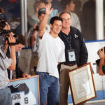 Paul Kariya , flanked by University of Maine President Peter Hoff,  waves to hockey fans after his No. 9 jersey was retired by the school during a ceremony at Alfond Arena in March 2009.