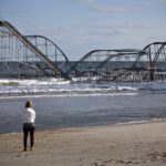 A woman looks at a roller coaster sitting in the ocean after Hurricane Sandy, in Seaside Heights, New Jersey, Nov. 28, 2012. The roller coaster was on part of a pier that collapsed in the storm.