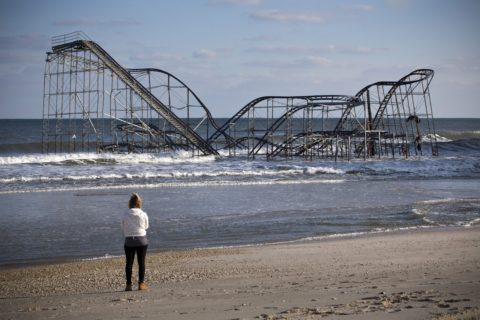 A woman looks at a roller coaster sitting in the ocean after Hurricane Sandy, in Seaside Heights, New Jersey, on Nov. 28, 2012. The roller coaster was on part of a pier that collapsed in the storm; climate change could contribute to such storms becoming more frequent.