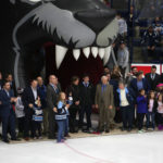 Members of the 1999 University of Maine national championship hockey team, along with some of their family members, are honored before the start of Maine's game against Boston University in November 2014 at Alfond Arena in Orono. Participating guests include (from left) Magnus Lundback, Steve Kariya, Robert Ek, Niko Dimitrakos, Anders Lundback, Eric Turgeon, Eilene Flaherty (obscured), Lynne Walsh, Sean Michael Walsh, Grant Standbrook, Andy Britt, Bobby Stewart (blue plaid shirt), Jimmy Leger (behind Stewart), Dan Kerluke, Marcus Gustafsson, Brendan Walsh (holding daughter) and Ben Guite (holding child).
