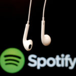 Headphones are seen in front of a logo of online music streaming service Spotify.