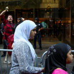 Muslim girls in hijabs walk past a man, as he shouts and gives a 'thumbs down' at activists (not pictured) protesting outside Trump Tower against the U.S. Supreme Court decision to revive parts of a travel ban on people from six Muslim-majority countries in Manhattan, New York, June 26, 2017.