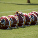 Washington Redskins helmets are lined up on the sideline during minicamp at Redskins Park.