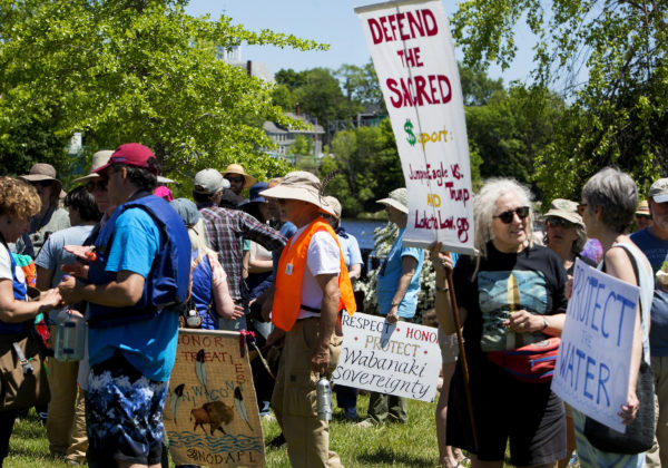 People gather during a rally in support of the Penobscot Nation's ongoing struggle to protect and enhance the water quality of the Penobscot River and watershed for the benefit of all at the Bangor Waterfront.