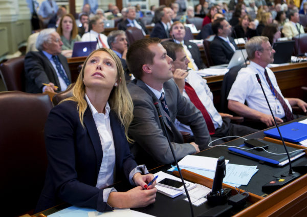 House Majority Leader Erin Herbig (left), D-Belfast, watches as votes come in during the House of Representatives vote on the state budget at the Maine State House in Augusta. Lawmakers are scurrying to avoid a state government shutdown.