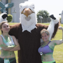 """Celebrate Husson! events kick off on Saturday, June 24 with a """"Run for the Gold."""" This fun run is divided into four major categories. For adults, there's a 5K run. There's also a student version of the 5K run.  In this photo, Husson's mascot congratulates two of last year's runners."""