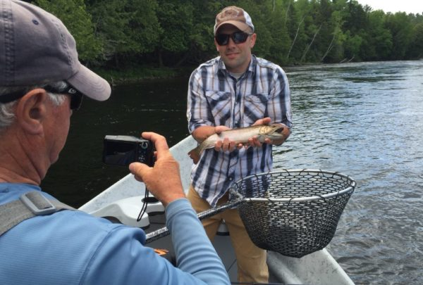 Dan Legere of the Maine Guide Fly shop snaps a photo as Brandon Prescott poses with the brook trout he caught on the East Outlet of the Kennebec River on June 18, 2017.
