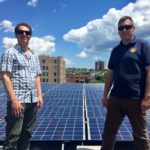 Bayside Bowl co-owner Justin Alfond (left) and Revision Energy's Josh Baston stand on the new roof amid the entertainment emporium's impressive solar array.