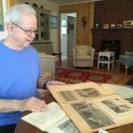 Rod McClure combs through a Bangor Little League scrapbook at his Brewer summer home on Monday. McClure has scrapbooks from the first two Bangor Little League baseball seasons in 1952 and 1953 that he is looking to find another home for.