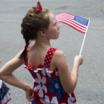BANGOR, Maine -- 07/04/2017 - Shayla Henderson, 8, waves her flag during the annual Fourth of July parade from Brewer to downtown Bangor on Tuesday. Ashley L. Conti   BDN